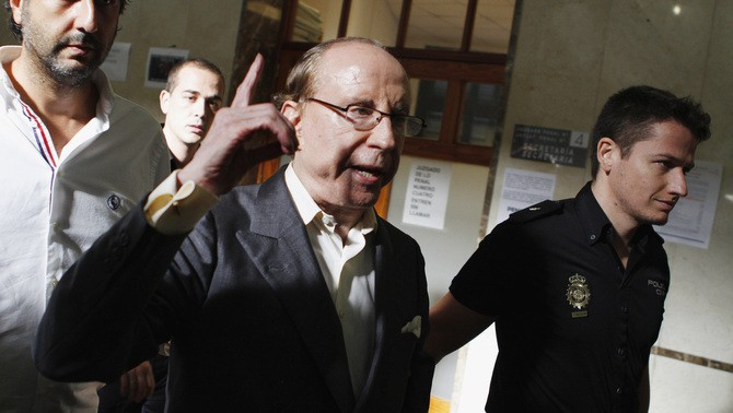 Spanish businessman Ruiz Mateos is escorted by a policeman as he arrives at the Court of Palma de Mallorca in Mallorca