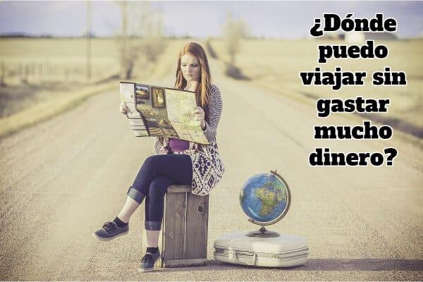 chica leyendo un mapa con las maletas en el suelo